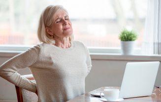 mulher com dor nas costas doenças reumáticas